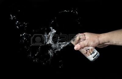 12002354 hombre tira el agua de un vaso sobre un fondo negro SUELTA EL VASO